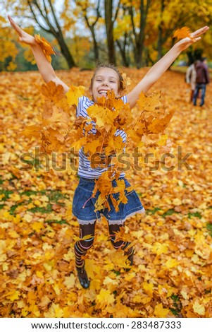 Little cheerful beautiful girl jumping on a background of yellow autumn maple leaves. - stock photo