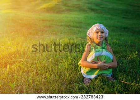 Little cheerful beautiful girl sitting on grass in summer city park. - stock photo