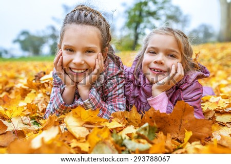 Little cheerful beautiful sisters buried in autumn maple leaves yellow. - stock photo
