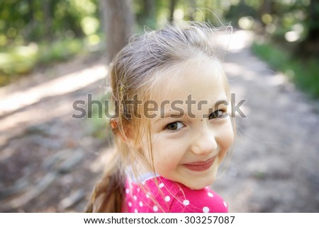 Little cheerful, big-eyed girl enjoying a hike through the woods, wandering and exploring nature. Active, outdoor lifestyle, family sports, quality time and happy childhood concept.  - stock photo