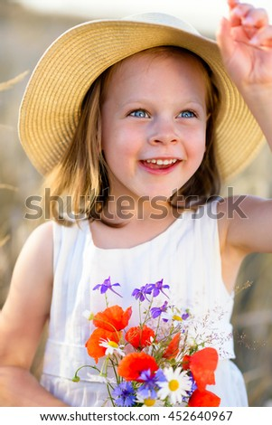 Little cheerful girl in a straw hat with wild flowers red poppy bouquet in the summer meadow - stock photo