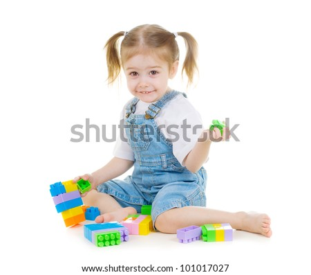 little cheerful girl in jeans plays with construction set over white background - stock photo