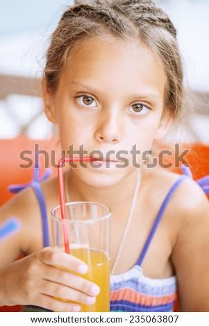 Little cheerful girl juice drink. - stock photo