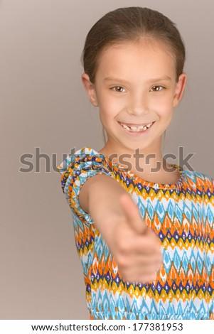Little cheerful girl lifts thumb upwards, on gray background. - stock photo