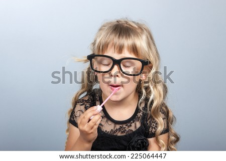 little cheerful girl paints lips with lipstick  mother's - stock photo