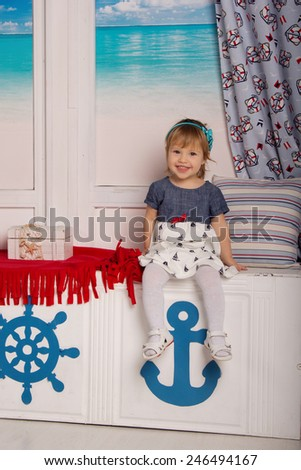 Little cheerful girl sailor in the sailor interior. Carefree childhood, game, entertainment - stock photo