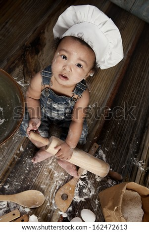 Little Chef.  Adorable baby boy dressed in s chef's hat.   - stock photo