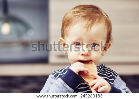 Little chef - boy with wooden spoon in the kitchen - stock photo