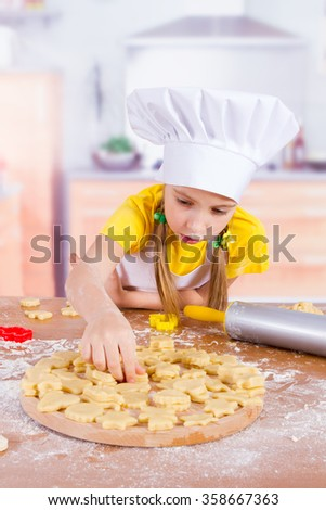 little chef girl lays on the Board from dough cookies - stock photo