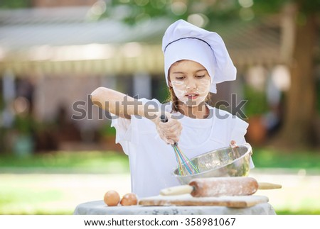 Little chef whipping eggs in a bowl outdoors - stock photo