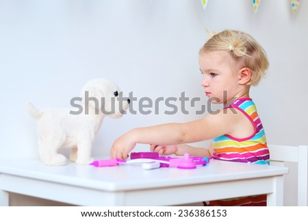 Little child, adorable blonde toddler girl, playing doctor role game treating her puppy sitting at small white table in playroom at home, school or kindergarten - stock photo