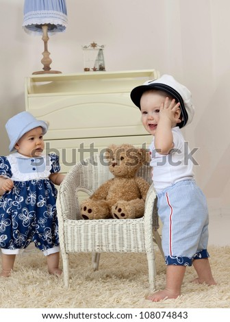 little child baby boy and girl standing near the chair  indoors in baby room playing - stock photo