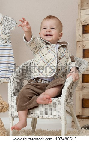 little child baby boy sitting on the chair indoors in baby room smiling happy - stock photo