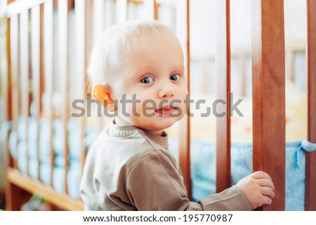 little child baby boy smiling standing near bed - stock photo