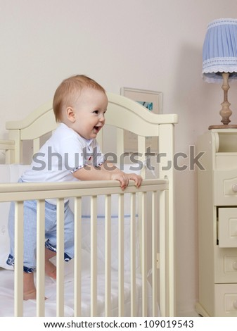little child baby boy standing in bed indoors in baby room smiling happy - stock photo