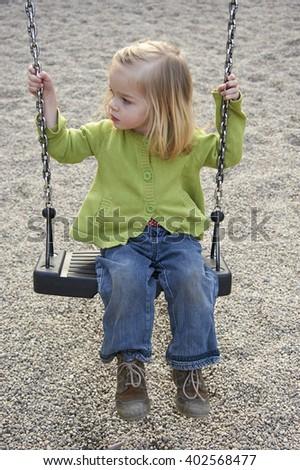 Little child blond girl having fun on a swing outdoor. Summer playground - stock photo