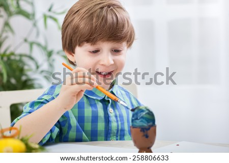 Little child boy painting eggs for easter - stock photo