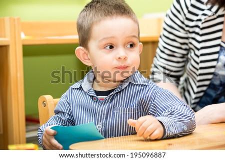 Little child boy playing in kindergarten in Montessori preschool Class. - stock photo