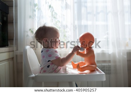 Little child, cute toddler girl having fun playing at home with her doll,playing with baby doll singing doll out  cup, takes care of the doll, casual lifestyle photo series in real life interior, - stock photo