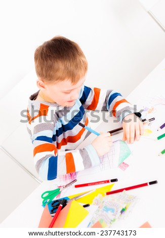 Little child drawing picture while sitting at white desk - stock photo