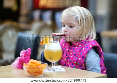Little child drinking juice cocktail with straw in outdoors cafe. Cute kid enjoying evening with family. - stock photo