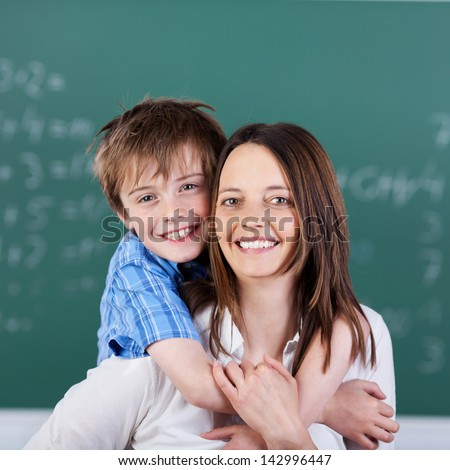 Little child embraced his mother inside the classroom - stock photo