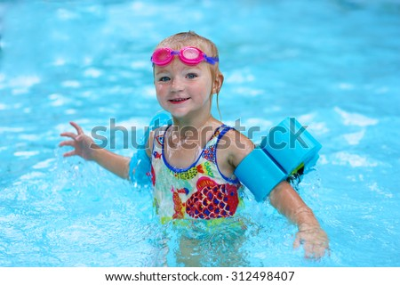 Little child enjoying swimming pool. Cute toddler girl wearing colorful swimsuit, pink goggles and blue armbands having fun in the water. Adorable sportsman kid promoting healthy lifestyle. - stock photo