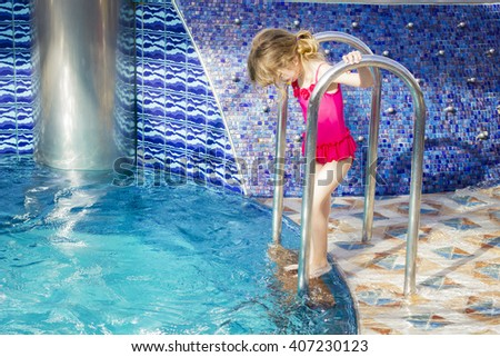Little child enjoying swimming pool. Cute toddler girl wearing pink swimsuit enters in the water. - stock photo