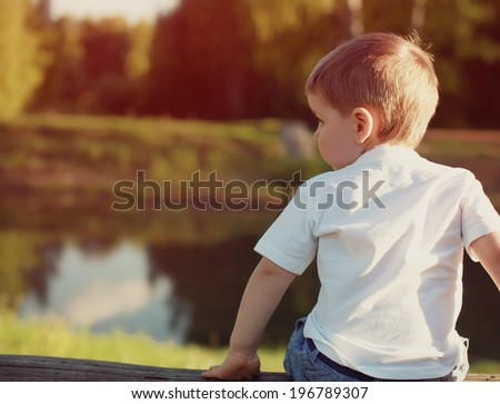 Little child from the back pensive looking away outdoors - stock photo