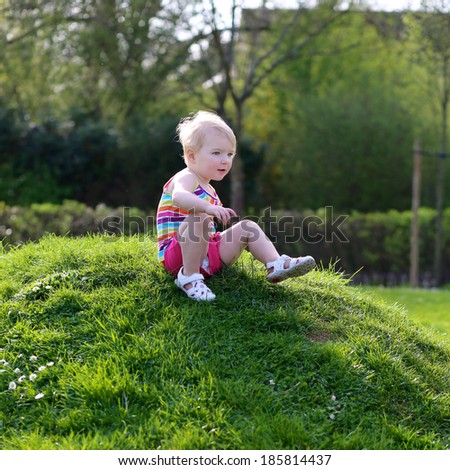 Little child, funny blonde toddler girl, playing in the park jumping on green lawn on a sunny summer day - stock photo