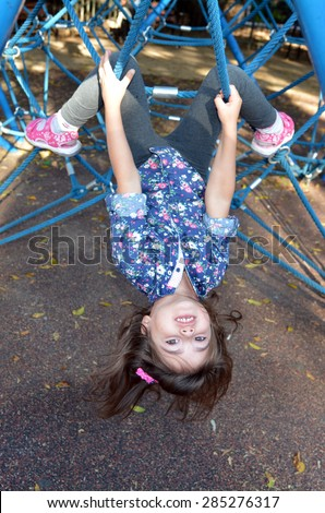 Little child (girl age 05) paly on spider web bar in a outdoor playground - stock photo