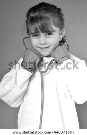 Little child (girl age 6) who wants to be a physician play pretend to be medical doctor in ambulatory care clinic looks at the camera.Medical concept with copy space. - stock photo