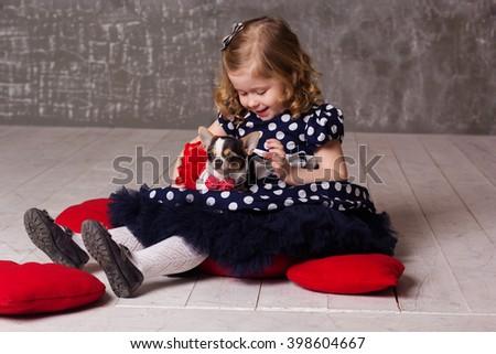 Little child girl is holding chuhuahua dog - stock photo