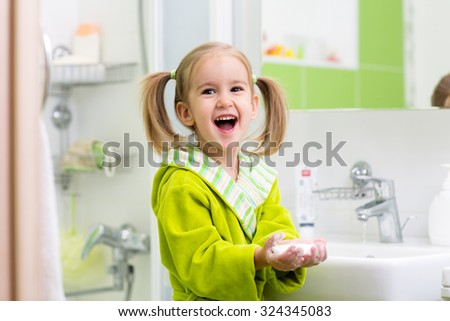 Little child girl washing her hands in bathroom. - stock photo