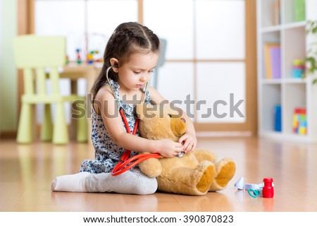 Little child girl with stethoscope and teddy bear sitting on floor, on home interior background - stock photo