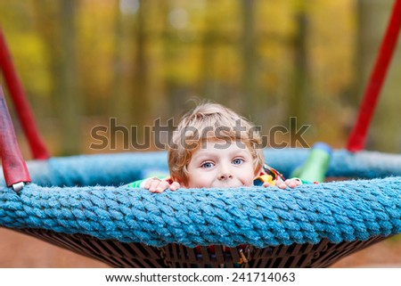 Little child in colorful rain jacket with stripes and gumboots having fun with playing chain swing on playground on warm, autumn day, outdoors - stock photo