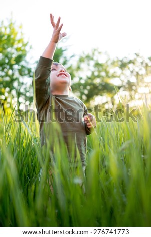 Little child in grass with hands up - stock photo