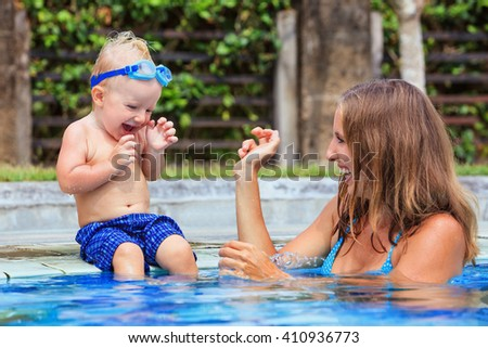 Little child in underwater goggles sit on poolside, has fun - baby splashing with mother in swimming pool. Family lifestyle and summer holiday water sports outdoor activity and lessons with parents. - stock photo