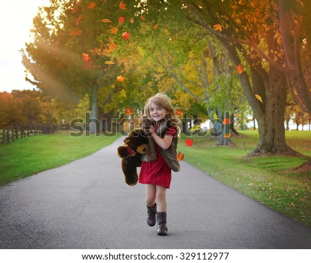 Little child is walking down a path with a Teddy Bear with Fall leaves and sunlight shining in the background - stock photo