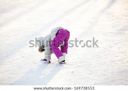 Little child learning ice skating - stock photo