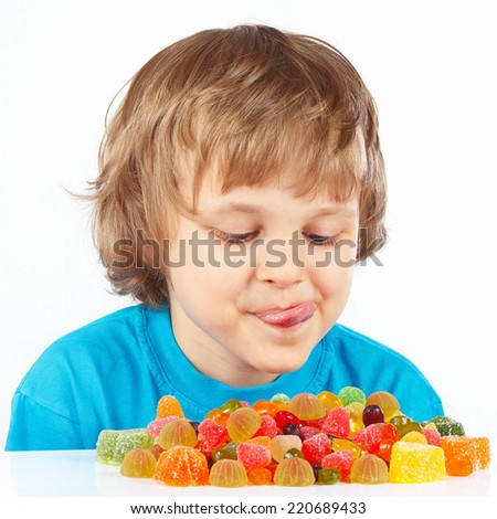 Little child looking at colored jelly candies on a white background - stock photo