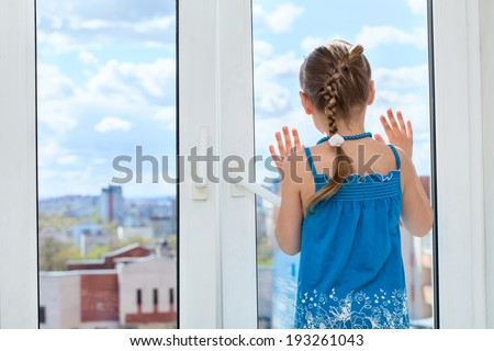 Little child looking through the window glass, copyspace, rear view - stock photo