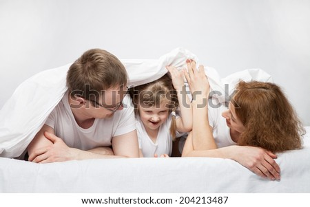 Little child lying in the bed between her parents, neutral background - stock photo