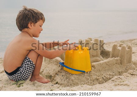 Little child making sand castles at the beach - stock photo