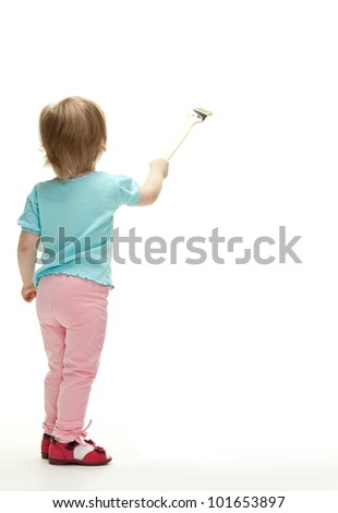 Little child painting white wall with a paintbrush, rear view full length portrait - stock photo