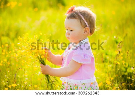 Little child playing with field flowers on spring or summer day. Beautiful little girl portrait at floral nature background. - stock photo