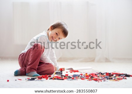 Little child playing with lots of colorful plastic blocks indoor, building a fire truck and a fire house, reading from a manual and imagining - stock photo