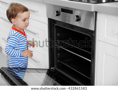 Little child playing with oven in the kitchen - stock photo