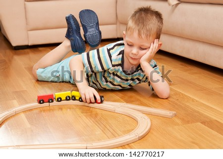 Little child playing with wooden railway on the floor. - stock photo
