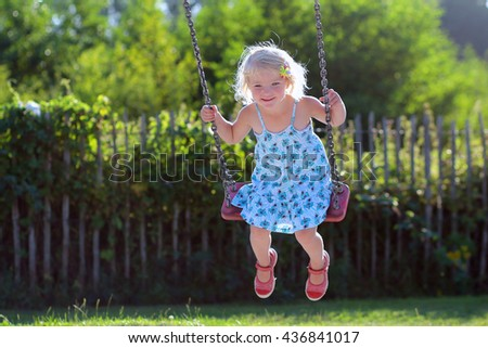 Little child swinging at playground. Happy toddler girl in blue dress playing outdoors on sunny day. Active kid enjoying summer vacation. Children leisure and education concept. - stock photo